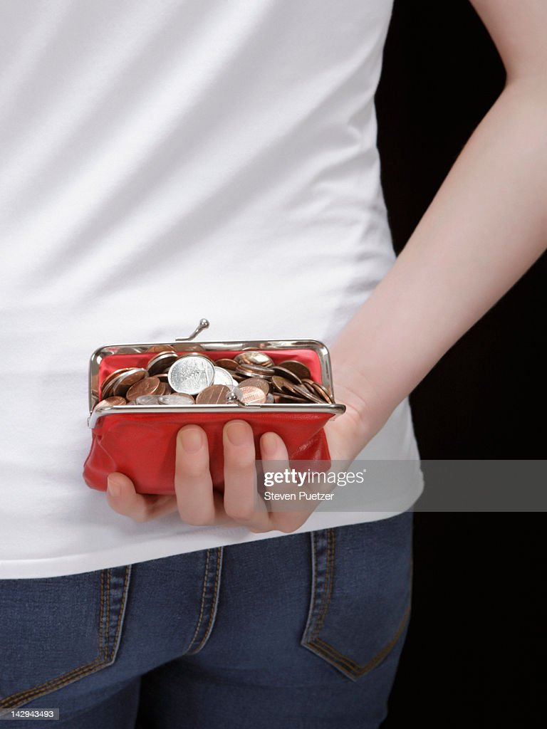 Woman holding red coin purse behind her back : Stock Photo