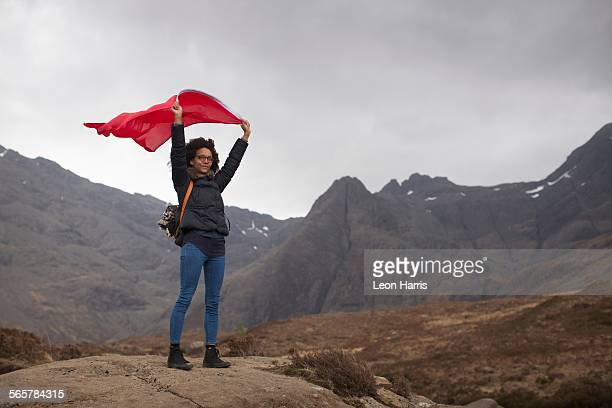 Woman holding red flag in mountains, Fairy Pools, Isle of Skye, Hebrides, Scotland