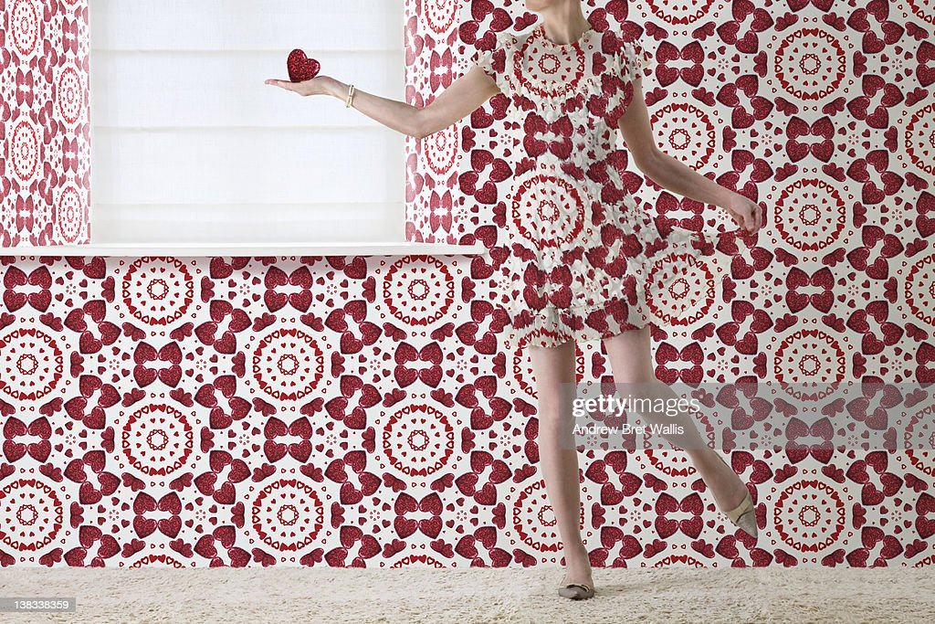 woman holding red heart blends into the wallpaper
