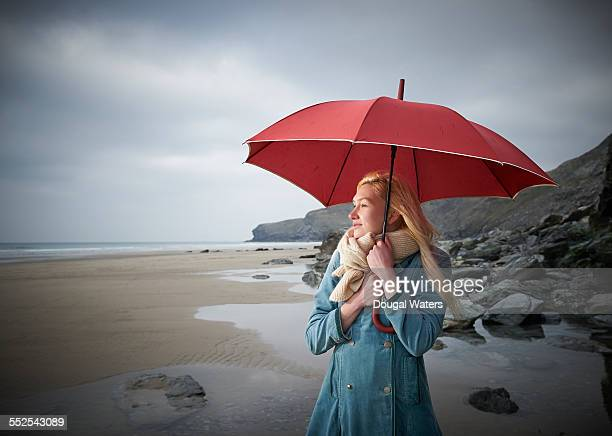 Woman holding red umbrella at beach.
