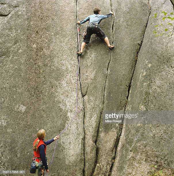 Woman holding rope, looking upward at partner climbing rock wall