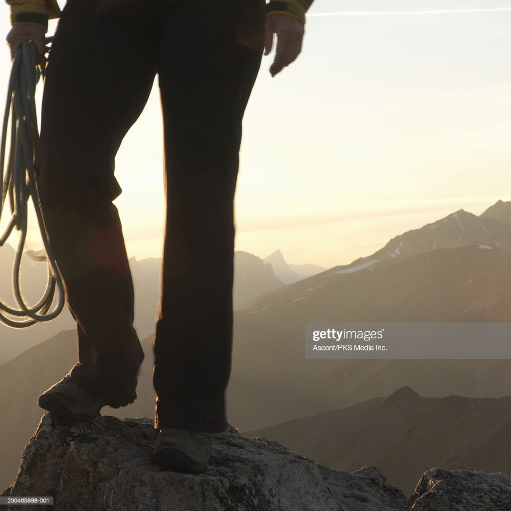 Woman holding rope, standing on rock in mountains, low section : Stock Photo