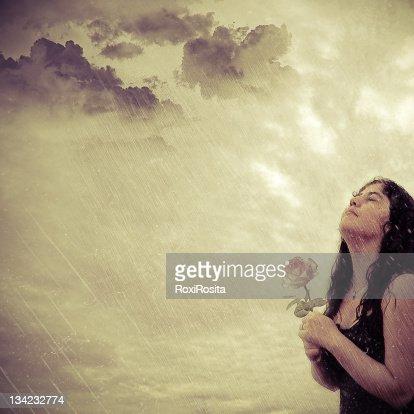 Woman holding rose in rain : Stock Photo
