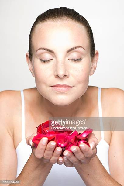 Woman holding rose petals in cupped hands, portrait