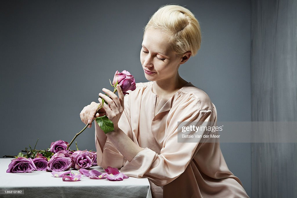 Woman holding rose, sitting at table. : Stock Photo