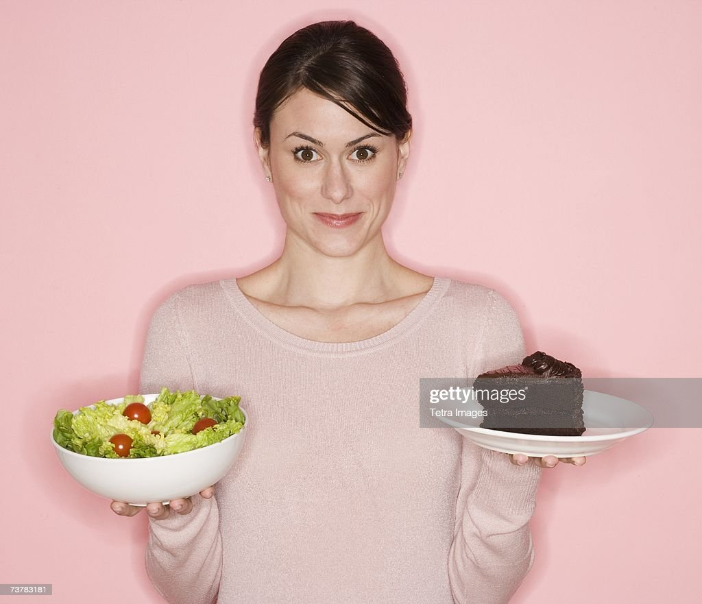 Woman holding salad and cake