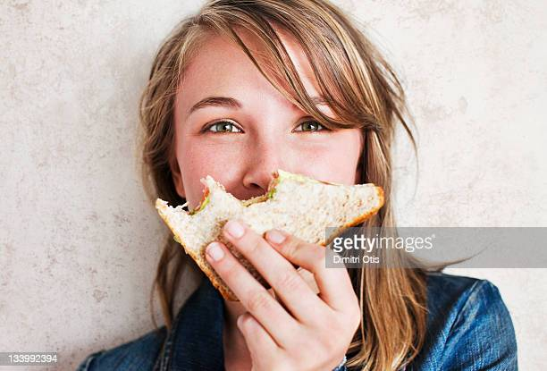woman holding  sandwich with bites taken from it