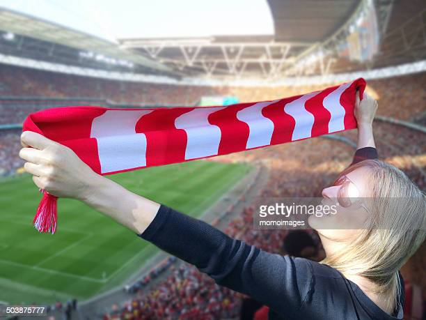 Woman holding scarf above head at sports event