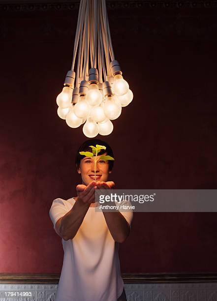 Woman holding seedling with bunch of lightbulbs