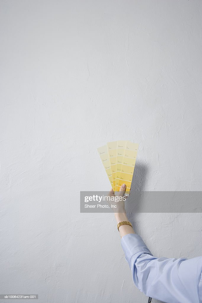 Woman Holding Set Of Yellow Color Samples In Front Of Wall