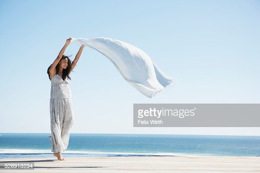 Woman holding shawl in wind : Stock Photo
