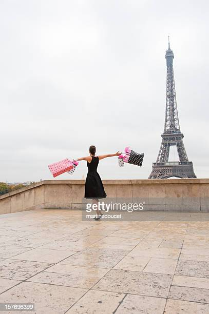 Woman holding shopping bags at the Eiffel Tower, Paris.