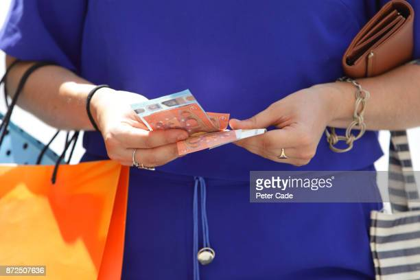 Woman holding shopping bags counting money