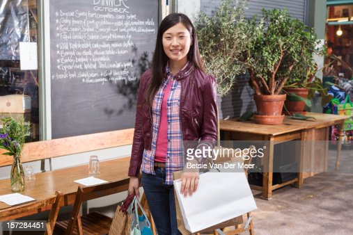 Woman holding shopping bags in front of cafe area. : Foto stock