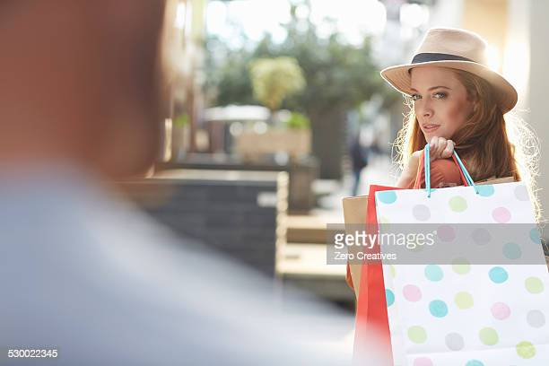 Woman holding shopping bags, looking over shoulder at man