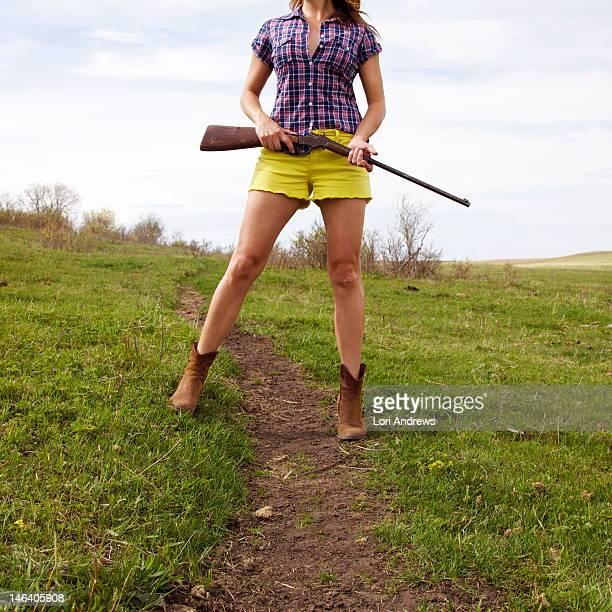 Woman holding shotgun in summer field