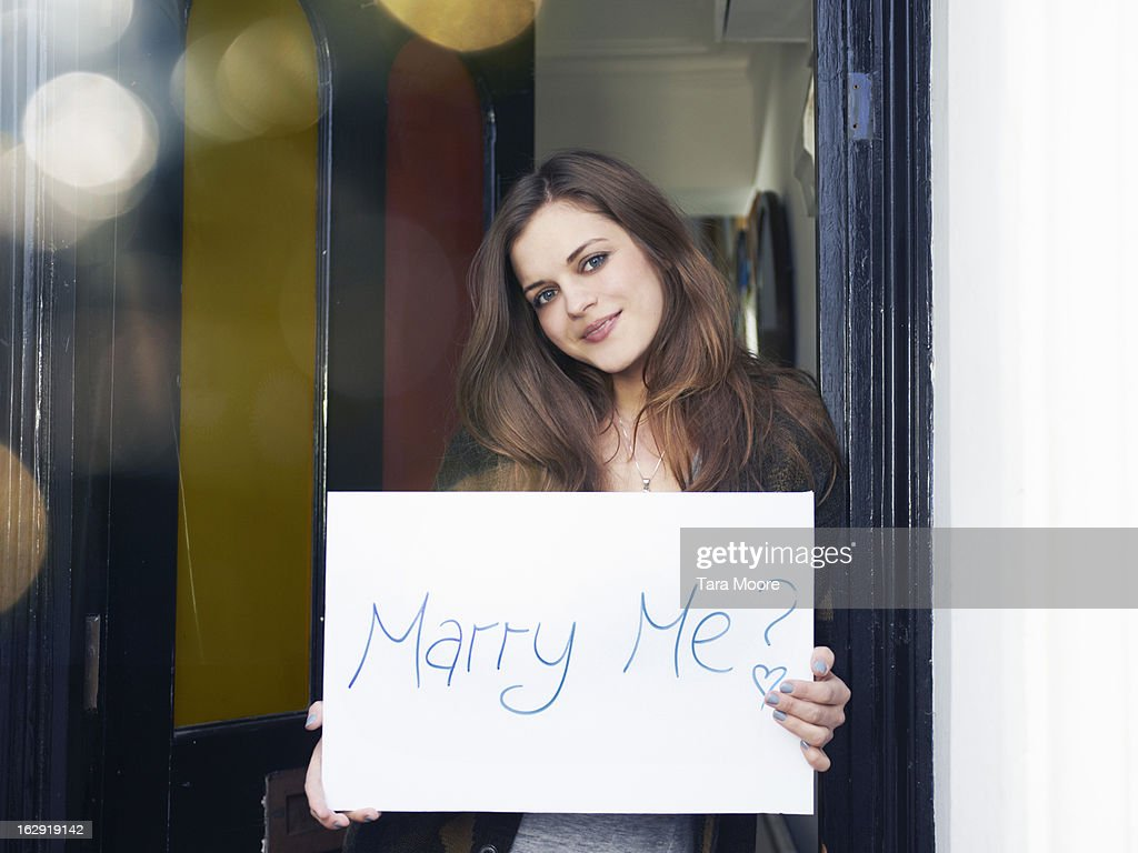 woman holding sign saying 'marry me?'