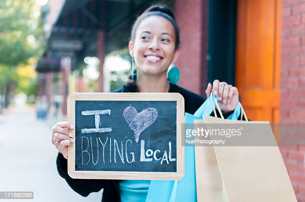 Woman holding sign that says I love buying local
