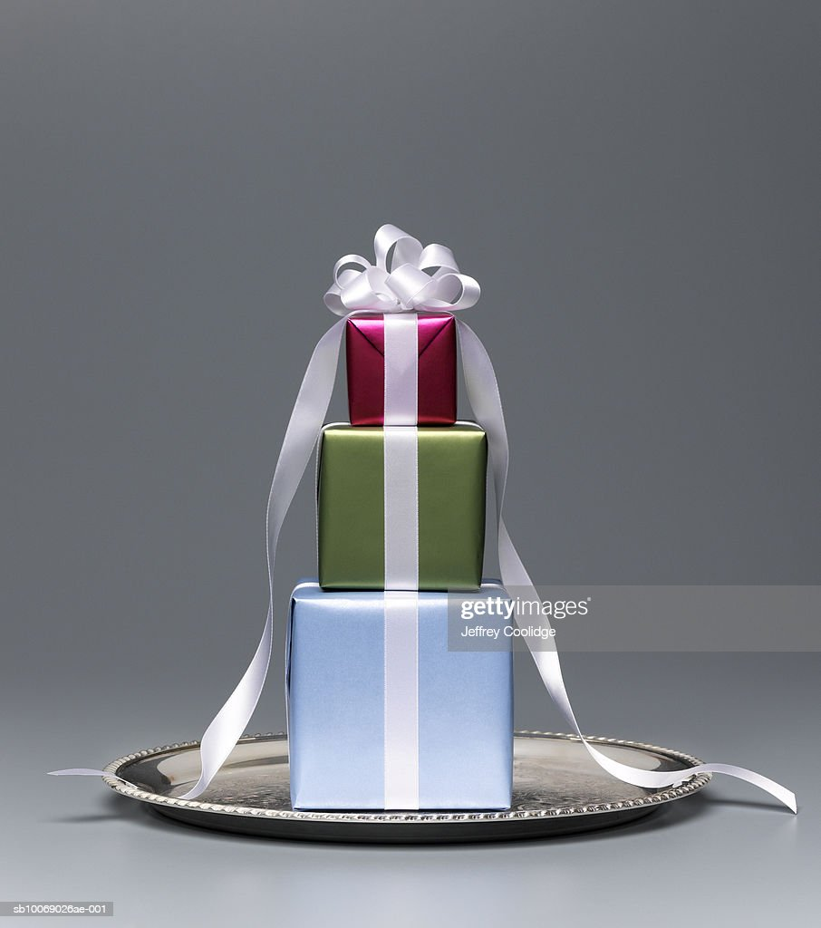 Woman holding silver tray with tree wrapped presents, mid section, studio shot : Stock Photo