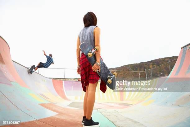 Woman holding skateboard at skate park