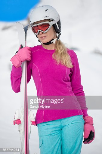Woman holding skis in snow, Crans-Montana, Swiss Alps, Switzerland