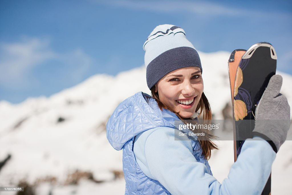 Woman holding skis