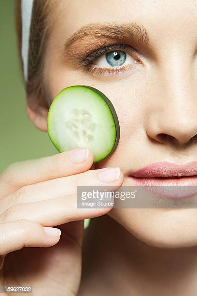 Woman holding slice of cucumber