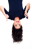 upside down view of young woman holding smart phone and giving thumb up