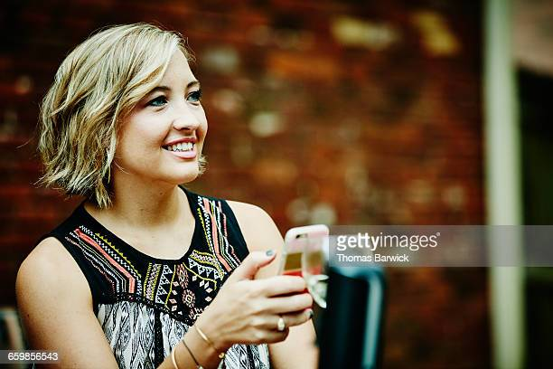 Woman holding smartphone hanging out with friends