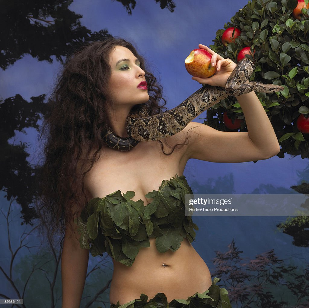 Woman holding snake and apple in garden