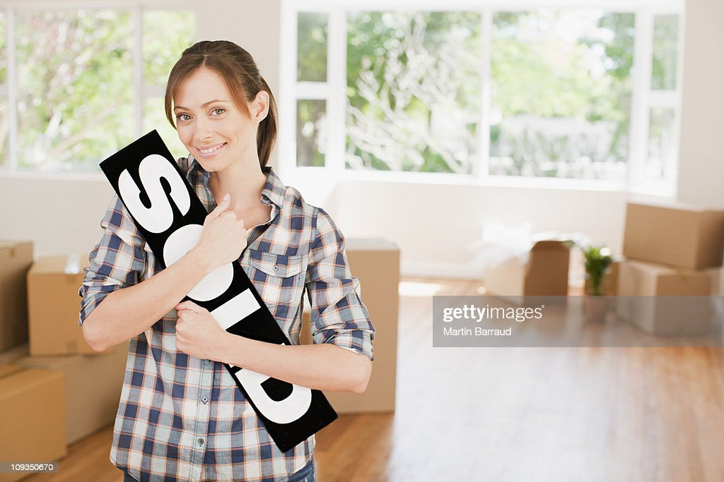 Woman holding sold sign in her new house : Stock-Foto