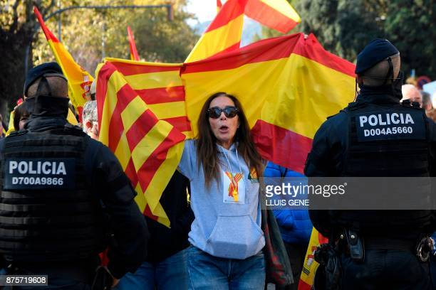 A woman holding Spanish and Catalan Senyera flags shouts slogans during a demonstration organised by fascist movements in Artos Square in Barcelona...