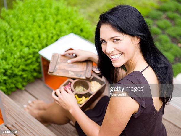 Woman holding spice box, smiling, elevated view