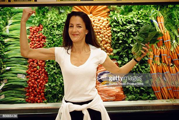 Woman holding spinach and flexing