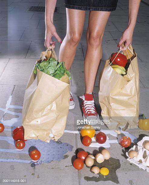 Woman holding split bags, groceries spilling on floor, low section