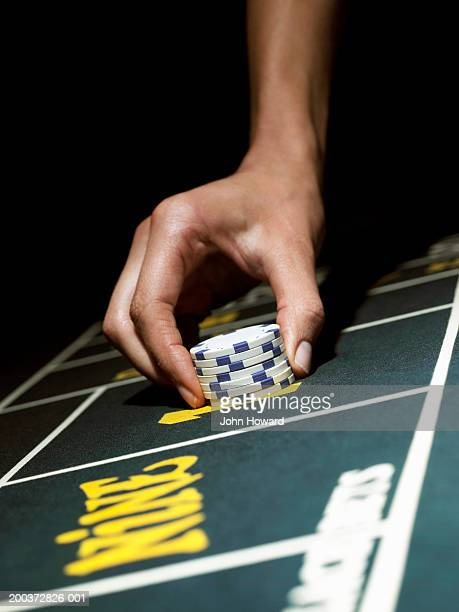 Woman holding stack of gambling chips on gaming table, close-up