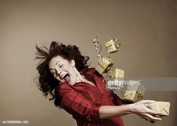 Woman holding stack of gift boxes, mouth open