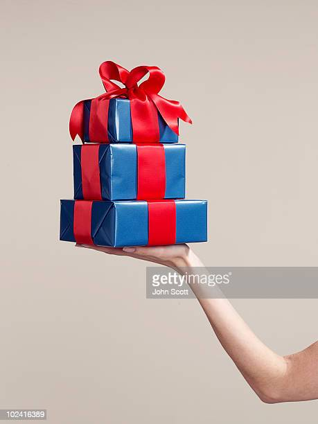 Woman holding stack of gifts