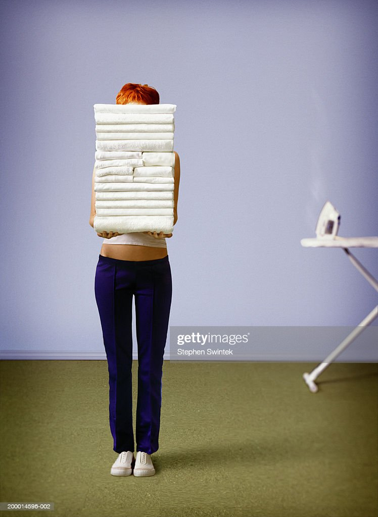 Woman holding stack of towels in front of face : Stock Photo