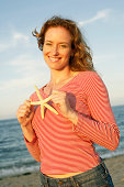 Woman holding starfish on beach