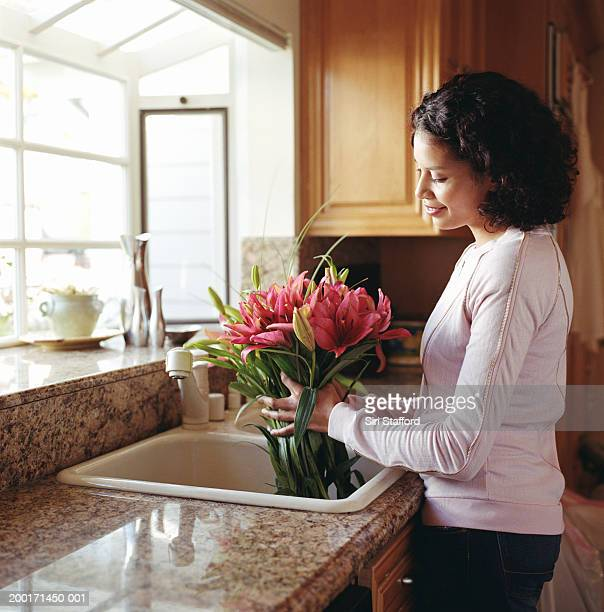 Woman holding stargazer lilies in sink