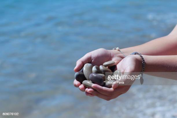 Woman holding stones in hands at beach.
