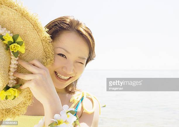 Woman holding straw hat