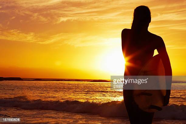 Woman holding surfboard against scenic sunset - Silhouette