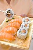 Woman holding sushi on plastic tray