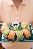 Woman holding sushi platter with soy sauce