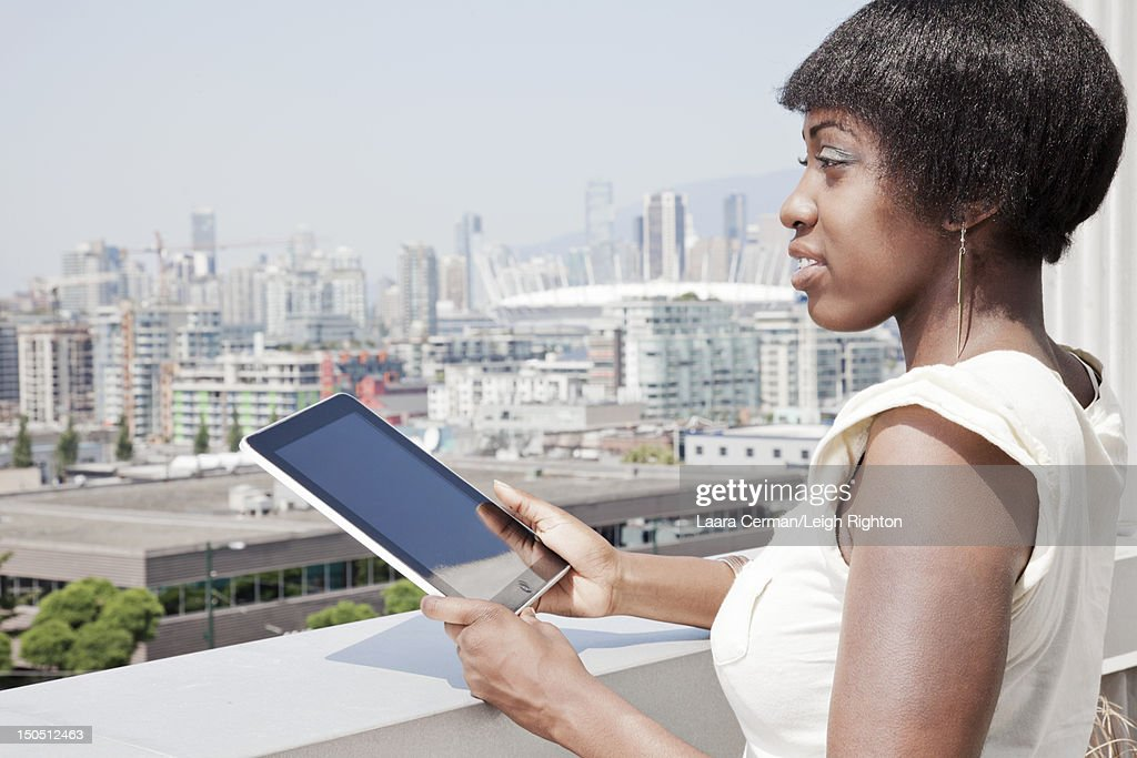 Woman holding tablet overlooking city. : Stock Photo