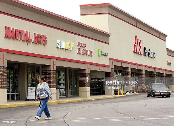 A woman holding the hand of a young child walks through a parking lot crosswalk of a shopping strip mall May 18 2005 in Palatine Illinois Strip malls...