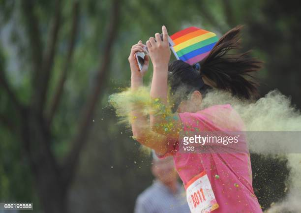 A woman holding the rainbow flag participates in the color run on May 21 2017 in Taiyuan Shanxi Province of China Around 300 people including about...