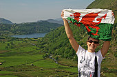 Woman holding the Welsh flag aloft at scenic lookout.